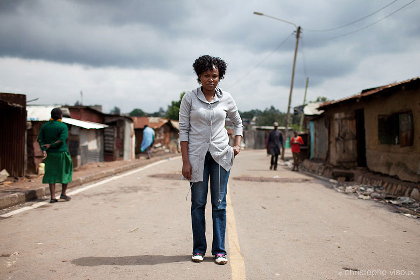 the journalist 'Chiku' is taking the pose on a street of one of largest slum in Nairobi: Korogocho