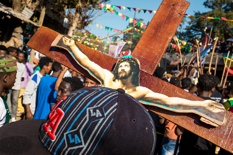 Timkat Gondar. A group leader is holding a Christian cross during the street procession of Timkat in Gondar